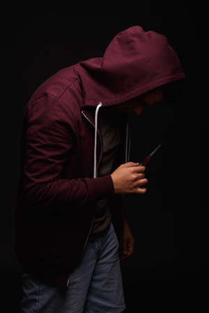 A guy with a drug addiction on a black background. Agonies concept. Young man in a burgundy jacket. Copy space. Stock Photo