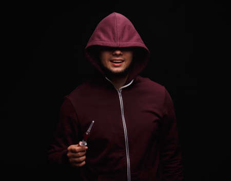 A young drug addict with a syringe on a black background. Portrait of young adult person with substance dependence.