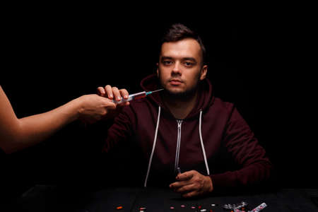 A junkie takes a syringe with drugs. A drug addicted on a black background. A young boy under the influence of drugs. Drug concept. Stock Photo