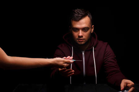 A junkie takes a syringe with drugs. A drug dealer on a black background. A young boy under the influence of drugs. Drug concept. Stock Photo