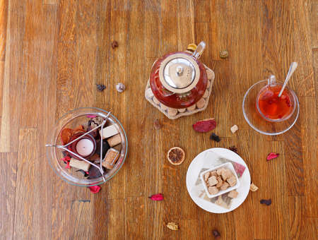 tea hot drink: Top view of a composition of traditional breakfast. A plate of powdered cookies, chocolate sweets and biscuits on a wooden table background. A cup of red tea and strawberry spicy tea in a kettle.