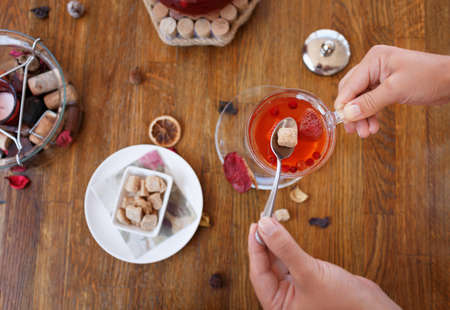 tea hot drink: Top view of a bowl of crunchy biscuits with nuts and spices on a wooden background. Womans hands holding a spoon with brown sugar and a cup of red, hot strawberry tea. A big and full tea kettle. Stock Photo