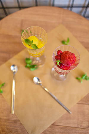 latticed: A view from above on refreshing sorbet scoops on a wooden table background. Two portions of bright juicy ice cream in crystal glasses. Summer desserts with decorative mint leaves. Copy space. Stock Photo