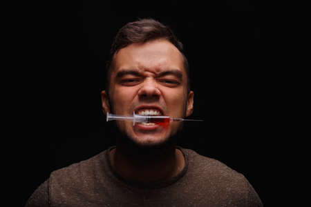 injectable: A junkie with drug addictions clamps between teeth a syringe with an injectable drug on a dark black background. Stock Photo
