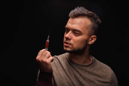 junky: An addicted junkie in a purple sweatshirt suffers from drug addiction with a syringe in a hand on a black background.
