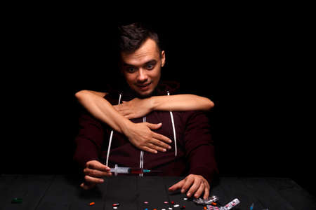 A crazy drug addict wants to inject drugs. A junkie on a black background. A young boy under the influence of drugs. Drug concept. Stock Photo