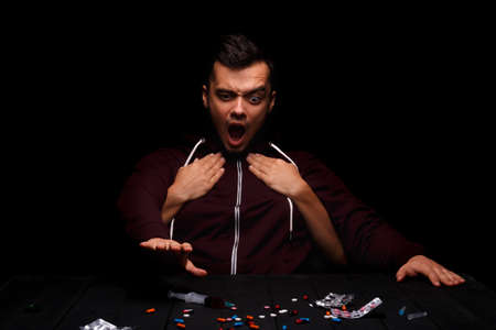 A screaming guy next to many drugs. A sick narcomaniac taking a syringe on a black background. Drug affection concept. Stock Photo