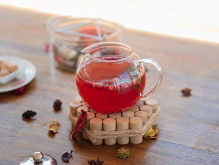 A spacious teapot with warm light red tea on a decorative stand. Chinese tea with peppermint and red berries standing on a wooden table, on a blurred light background. Healthy breakfast drink.