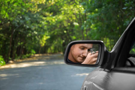 violación: A driving man with an alcohol in a rearview mirror on a blurred background. Drinking and driving concept. Copy space. Foto de archivo