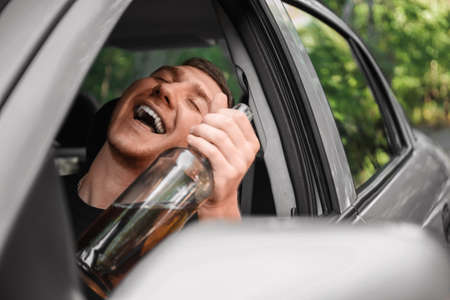Drunk man driving. Irresponsible student with a bottle of beer in a car on a blurred background. Alcohol abuse concept.