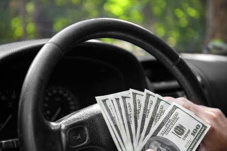 Close-up of american dollars on a wheel. A man driving with money on a car background. Investment and savings concept. Archivio Fotografico