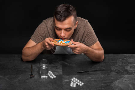 A hopeless junkie swallows drugs. A drug addicted sitting at the table on a black background. Drug concept. Copy space. Stock Photo