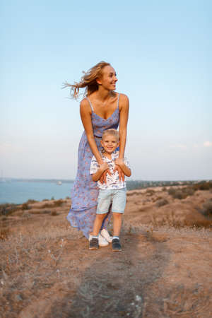 A stunning female with her kid on a natural background. Happy family together. Motherhood and childhood.