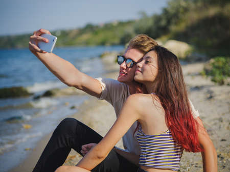 Close-up of a beautiful girl and a fellow taking a selfie on a riverbank on a natural blurred background.