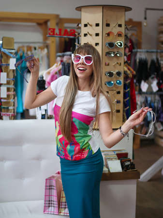 A cheerful lady trying on trendy glasses on a blurred shopping store background. A woman in a shopping mall. Stock Photo