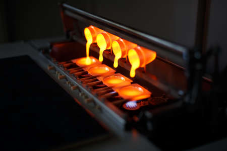Staal smelt en oxideert onder hoge druk en temperatuur. Vier kopjes vol gesmolten gloeiend goud, gieten in speciale vormen op een wazige industriële achtergrond. Gevaarlijke productieapparatuur. Stockfoto - 84987050