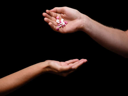 Two hands exchanging little pink and white tablets on the black background. A doctor giving healthy pills full of vitamins to a sick female patient, close-up. Professional healthcare concept.