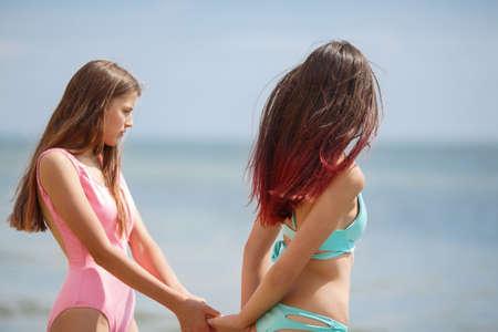 青い海の背景にカラフルな水着で 2 人の美しく、セクシーな女の子の写真。海のビーチで休んで長い髪で良い形に若い女性は。夏の休日や休暇の概