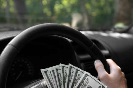 Close-up picture of money on a black wheel of a new modern car and mans hands driving it. A man holding cash in american dollars on a car background. Corporate business and transactions concept.
