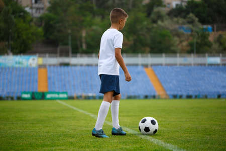 A full-length photo of a cute football player wearing white sporty clothes on a stadium background. A round football ball on a bright green grass. Sports, activities, healthy and people concept.