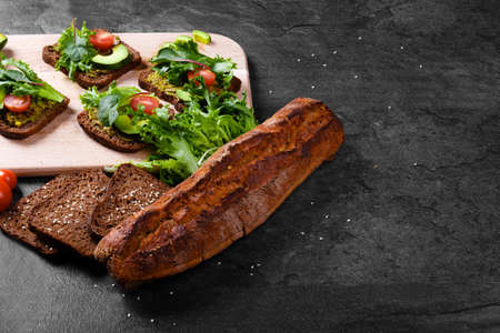 lose-up picture of rustic, freshly baked, crunchy and crispy sliced black baguette bread on a black table background. Bread next to a cutting desk with vegetable sandwiches and green arugula leaves.