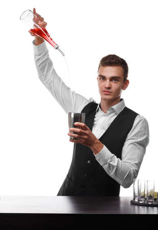 An attractive bartender at a bar counter doing a cocktail, a plate of lime isolated on a white background.