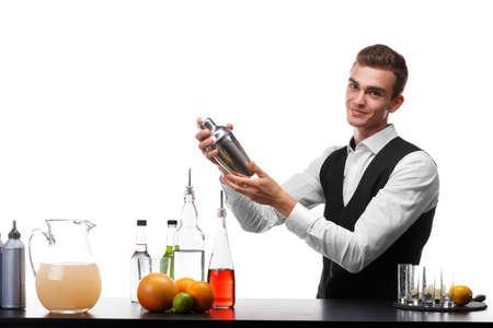 Un barman atractivo con una coctelera en una barra contraria, cal, naranjas, limones aislados en un fondo blanco.
