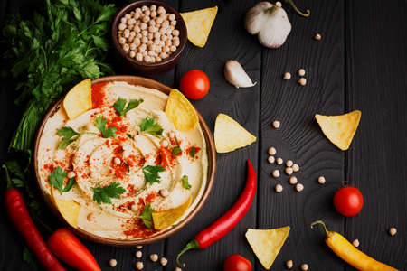 A view from above on a nutritious hummus appetizer on a black wooden table background. A traditional dish spread over a wooden plate. A tasty snack next to a bowl of chickpeas, nachos, and vegetables. Archivio Fotografico