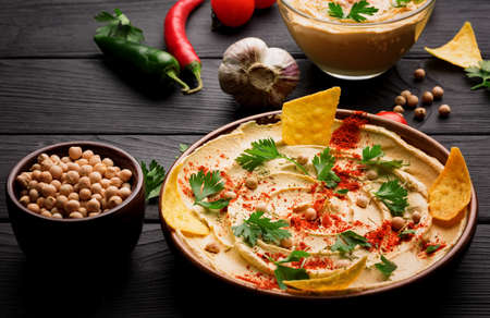 A close-up picture of a nutritious hummus appetizer on a black wooden table background. An arabic traditional dish spread over a dark brown wooden plate. A tasty snack next to a bowl of chickpeas.