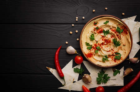 Top view of a plate of hot, fresh hummus and sliced pita bread on a black wooden background. Hummus with parsley leaves, chilli pepper ad cherry tomatoes. Natural mediterranean appetizers. Copy space. Archivio Fotografico