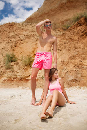 An attractive fellow stands near a beautiful girl in a pink swimsuit on a beach on a natural blurred background.