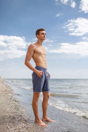 A full-length portrait of a sexy boy with a muscular torso stands on a seashore on a natural blurred background.