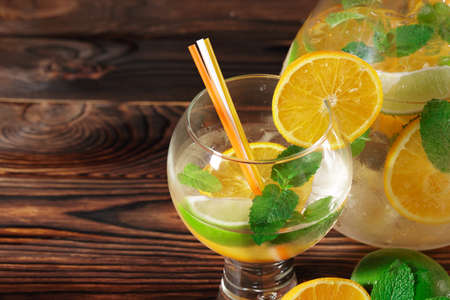 Close-up picture of a glass of a cold, fruity, sweet alcoholic beverage with citrus slices and crushed ice. Glass of cocktail next to a jar with spicy mint and fruit drink on a wooden background.