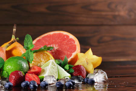 Fresh yellow carambola, red strawberries, lime, mint leaves, grapefruit on a blurred wooden background. Stock Photo