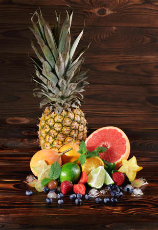 A wooden table with oranges, blueberries, pineapple, bright juicy grapefruit, cubes of ice, lime, pears, red strawberries and yellow carambola on a brown wooden background.