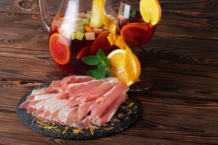 A plate of prosciutto and ham, a glass jug of beverage with apples and oranges on a wooden brown background. Stock Photo