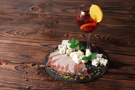 A wooden table with a plate of shhep milk blue cheese Roquefort and thinly sliced prosciutto with green leaves of mint, a glass of fruit drink on a wooden background. Stock Photo