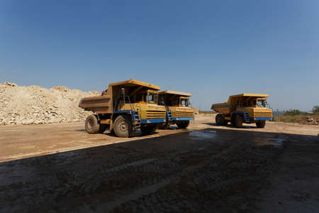 sand quarry: Dump trucks, dumper or tipper trucks in a sand quarry, transporting loose materials on a natural background. Stock Photo