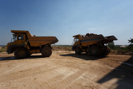 buildingsite: Dump trucks, dumper or tipper trucks in a sand quarry, transporting loose materials on a natural background. Stock Photo