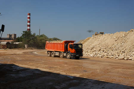 sand quarry: An orange dump truck, lorry full of stones in a sand quarry, transporting of materials on a natural background.