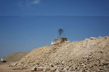 sand quarry: A backhoe loader, a loader backhoe, digger on a heap of sand and stones on a natural background.