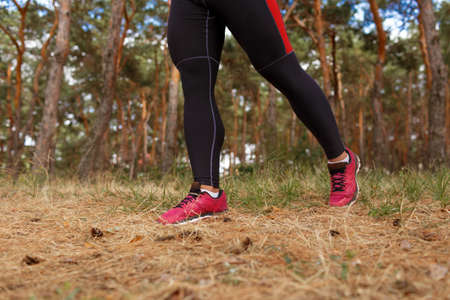Strong muscular legs of an athletic man doing warming-up exercises on a blurred natural background. Stock Photo