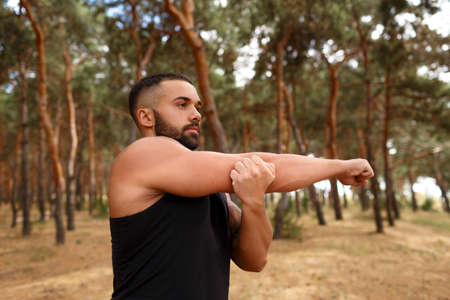 A man with strong muscular body doing warming-up exercise on a blurred natural background.