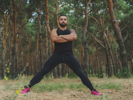 A handsome man with stubble doing stretching exercises in a forest. Sexy, hot muscular sports man walking in the park. A sexy muscular man on a natural background. Sports concept. Stock Photo