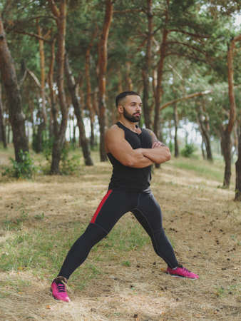 A handsome man with stubble doing stretching exercises in a forest. Sexy, hot muscular sports man walking in the park. A sexy muscular man on a natural background.