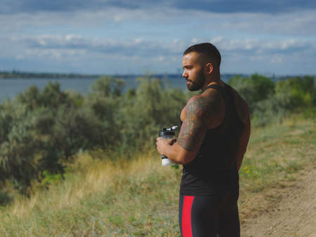 A muscular handsome bodybuilder with a tattoo on his shoulder drinking water after a workout on a natural background.