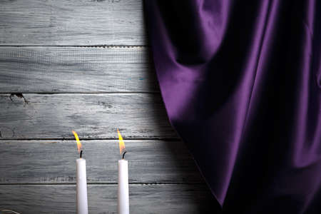 A silk purple curtain, two burning candles, romantic evening with beloved on a light gray background.