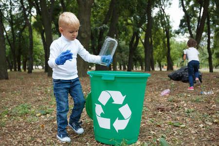 Een klein kind dat het huisvuil in een groene recyclingsbak op een vage natuurlijke achtergrond zet. Ecologie vervuiling concept.