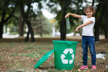 A little child putting the garbage in a green recycling bin on a blurred natural background. Ecology pollution concept. 版權商用圖片 - 85414811