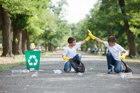 Two cute boys cleaning up the territory and giving each other five on a blurred park background. Ecology protection concept.